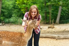 Young woman stroking a deer Royalty Free Stock Photo