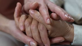 Young woman stroking hands of pensioner, caring for old parents, compassion