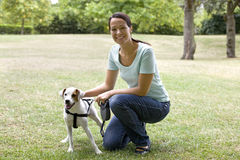 A young woman stroking her dog in the park Stock Photography