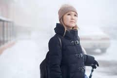 Young woman with stroller walking in winter, looks thoughtfully at sky. Young woman with a stroller on a walk in the winter looks thoughtfully at the sky Stock Images
