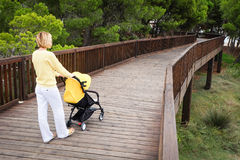Young woman strolling a baby carriage on wooden bridge. In green park. Back view Royalty Free Stock Image