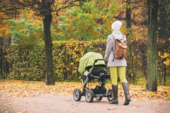 Young woman strolling carriage outdoors. In park Royalty Free Stock Images