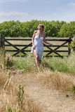 Young woman strolling in the countryside in summer Stock Photos