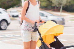 Young woman strolling pushchair with a baby by the city street Stock Image
