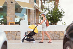 Young woman strolling pushchair with a baby by the city street. Young woman strolling pushchair with baby by the street. Some cars on foreground. Street cafe on Stock Photography