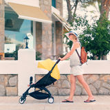 Young woman strolling pushchair with sleeping baby Stock Images
