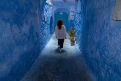 A young woman strolls through the streets of Chefchaouen, the blue town in Morocco, between the walls and the blue arches stock photo