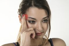 A young woman is struggling with pain, isolated on background Stock Photography