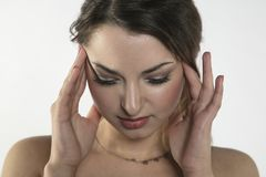 A young woman is struggling with pain, isolated on background Royalty Free Stock Image