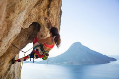 Young woman struggling to climb ledge on cliff. Against view of sea and island royalty free stock images