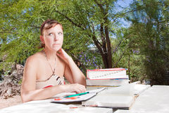A young woman stuck whilst studying. This attractive young lady has a comical look as she studies Royalty Free Stock Image
