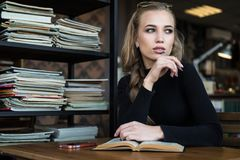 Young woman student, bored to read book in a library.  Stock Photography