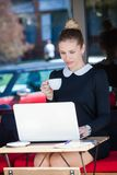Young woman student or business sit and drink coffee in cafe out. Young elegant woman student or business sit and drink coffee in cafe outdoor use  laptop Stock Photo