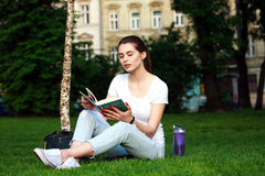 Young woman student in a city park reading a book Stock Image