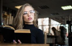 Young woman student in eyeglasses, bored to read book in a library.  Stock Photo