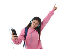 Young woman or student girl with mobile phone listening to music headphones singing and dancing Royalty Free Stock Images