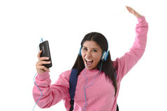 Young woman or student girl with mobile phone listening to music headphones singing and dancing Stock Photos
