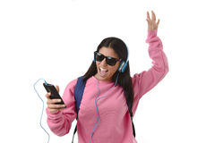 Young woman or student girl with mobile phone listening to music headphones singing and dancing Stock Images
