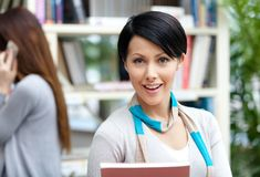 Young woman student at the library against bookshelves Royalty Free Stock Image
