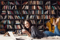 Young woman student in library at home lying drinking coffee stock image