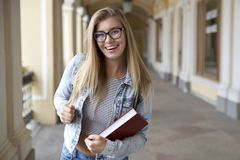 Young woman student with long hair and glasses happily dancing e Royalty Free Stock Image