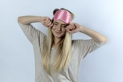 A young woman or a student in pajamas and a blindfold yawns and royalty free stock image