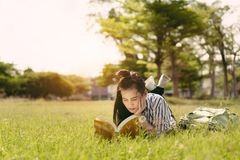Young woman student reading book in university. Campus college and serious study learning knowledge at park outdoor Stock Images
