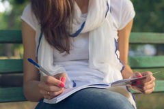 Young woman student sitting on a bench in the Park. Young female student sitting on a bench in the park. She takes notes in a notebook. She is dressed in blue Stock Photos