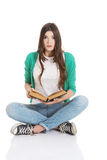 Young woman student sitting and reading a book. Stock Photo