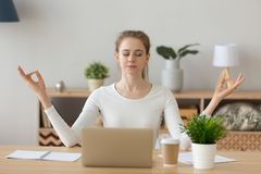 Young woman student taking break meditating at home office desk. Young woman student taking break doing yoga exercise at home office desk focusing on stock photo