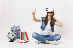 Young woman student in virtual reality glasses touch something like push on button, pointing at floating virtual screen. Near globe backpack school book stock photography