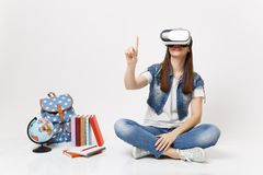 Young woman student in virtual reality glasses touch something like push on button, pointing at floating virtual screen. Near globe backpack school book stock photos