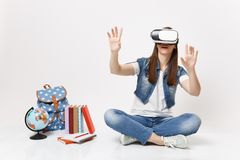 Young woman student in virtual reality glasses touch something like push on button, pointing at floating virtual screen. Near globe backpack school book royalty free stock images