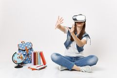 Young woman student in virtual reality glasses touch something like push on button, pointing at floating virtual screen. Near globe backpack school book royalty free stock photo