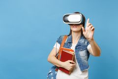 Young woman student in virtual reality goggles hold books touch something like push on button, pointing at floating. Virtual screen isolated on blue background royalty free stock image