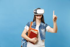 Young woman student in virtual reality headset hold books touch something like push on button, pointing at floating. Virtual screen isolated on blue background stock photos