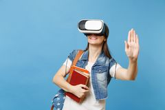 Young woman student in virtual reality headset hold books touch something like push on button, pointing at floating. Virtual screen isolated on blue background royalty free stock photos