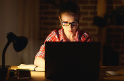 Young woman student working on the computer at night. Young woman girl student working on the computer at night at home Royalty Free Stock Image