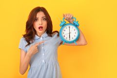 Young woman studio isolated on yellow holding alarm clock pointing at time royalty free stock images