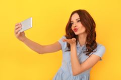 Young woman studio isolated on yellow taking selfie pictures stock images