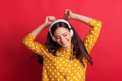 A young woman in studio with white headphones, hands in the air. stock photos