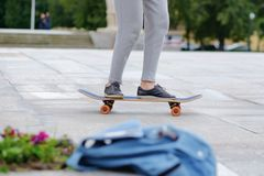 Young woman study skateboarding at city. She uncertainly tries to drive forward Stock Photos
