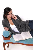 Young woman studying. Isolated picture of a young woman studying while talking on the phone Stock Photography