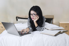Young woman studying on the bed Royalty Free Stock Photos