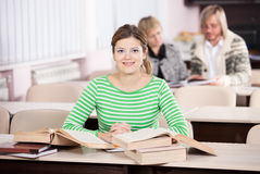 Young woman studying at desk with lots of books Stock Photo