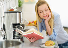 Young woman studying in kitchen Stock Photos