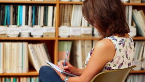 Young woman studying in library with notepad Stock Image