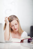Young woman studying from a textbook. Sitting at a table concentrating on her reading with her head resting on her hand Royalty Free Stock Images