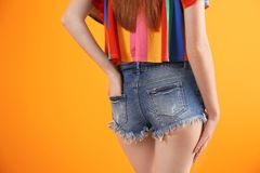 Young woman in stylish jean shorts. On color background royalty free stock images