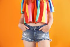 Young woman in stylish jean shorts. On color background stock images